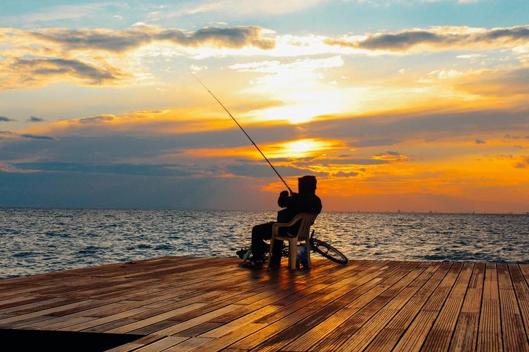 man fishing on a wooden deck during sunset