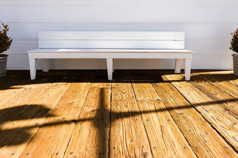 white bench placed on a wooden deck