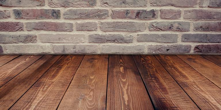 view of a brick wall on top of wooden floor