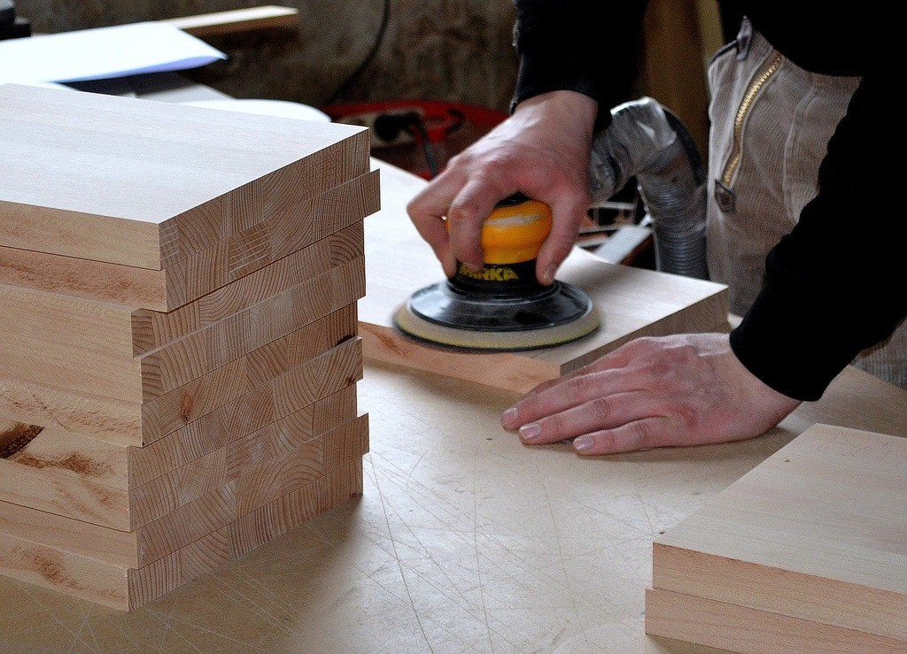 man using a planer on wood
