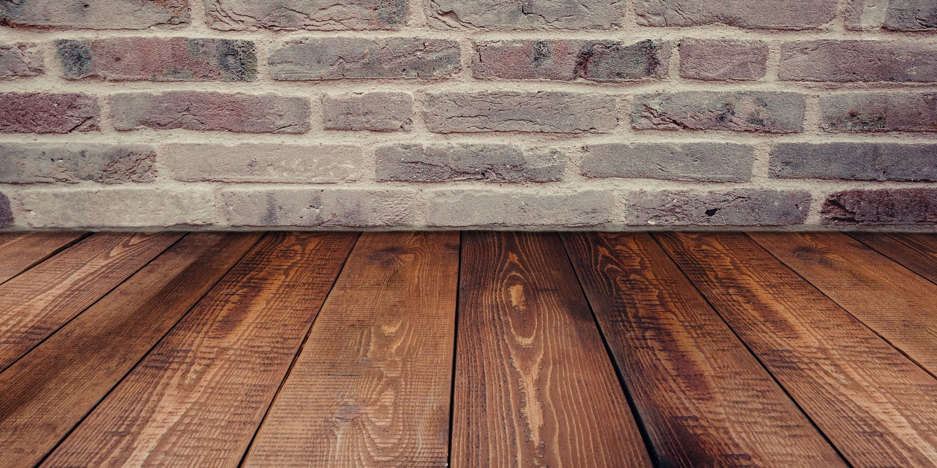 picture of stained wooden floors and a brick wall